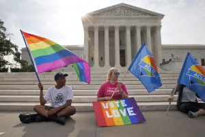 Carlos McKnight, 17, of Washington, left, and Katherine Nicole Struck, 25, of Frederick, Md., hold flags in support of gay marriage outside of the Supreme Court in Washington, Friday June 26, 2015. A major opinion on gay marriage is among the remaining to be released before the term ends at the end of June. (AP Photo/Jacquelyn Martin)